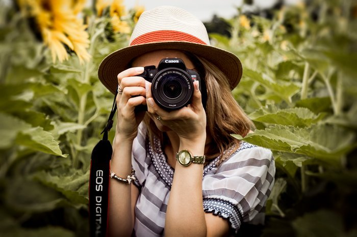 A girl in a sunflower field taking a photo with a DSLR camera