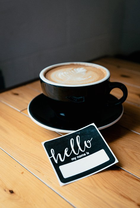 A coffee cup beside a name badge