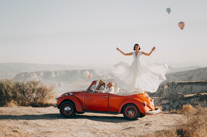 Fun wedding portrait of the bride standing on the back of a car in the desert
