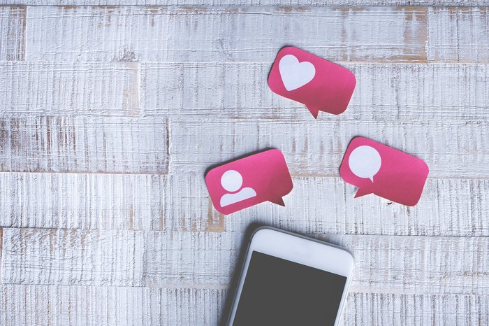 A smartphone with pink paper social share and likes icons above it