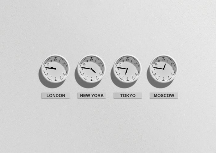Four white clocks set to London, New York, Tokyo, Moscow Timezones