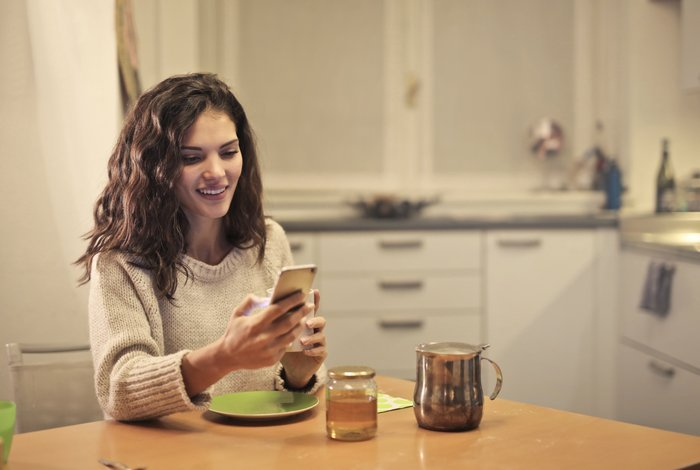 A girl using her cellphone at the breakfast table