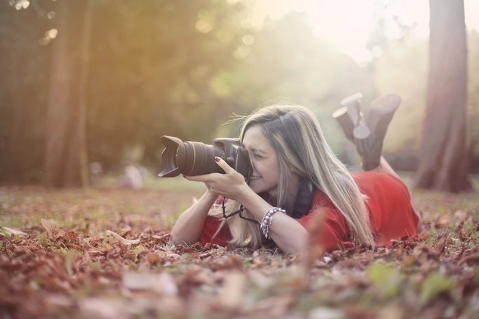 A girl lying in autumn leaves to take a photo with a DSLR