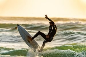 photo of a surfer trying to catch a wave