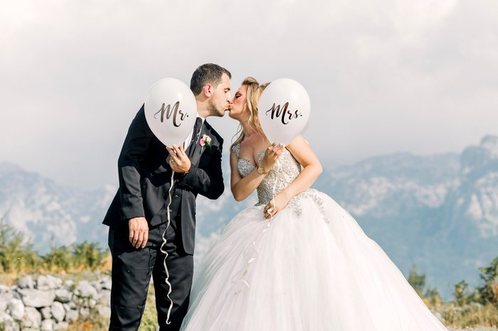 Cute wedding portrait of the bride and groom posing with balloons