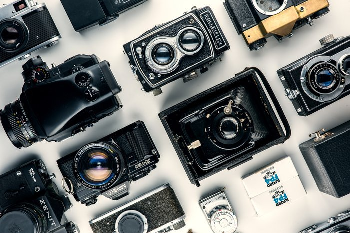 Various cameras laid out on a table