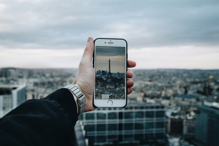 A person taking a photo of the Eiffel tower with a smartphone
