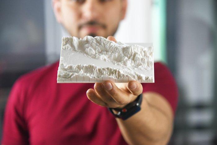 a photo of a nan holding a landscape 3d print