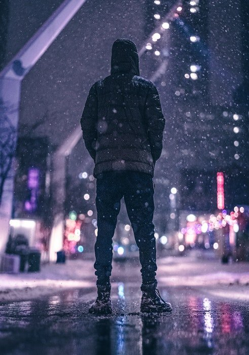A man in winter clothes standing on a city street while its snowing