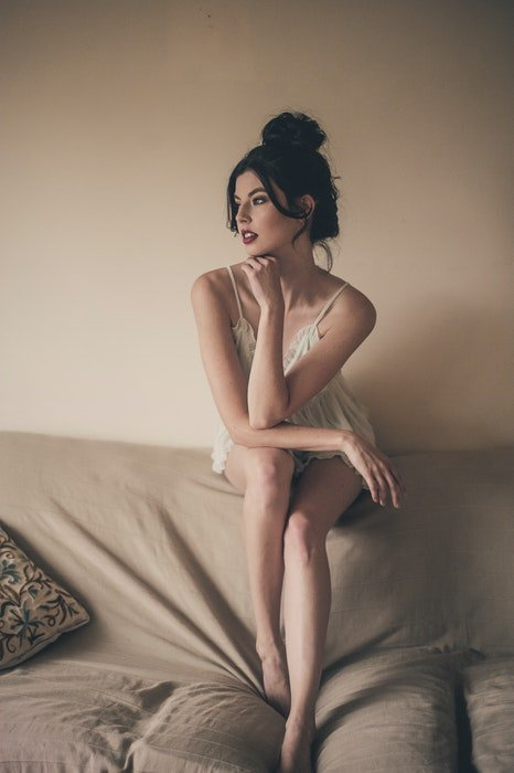 A girl in white lingerie posing on a couch for a bridal boudoir photoshoot