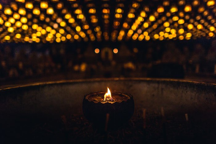 A close up of a tealight candle in a dark room