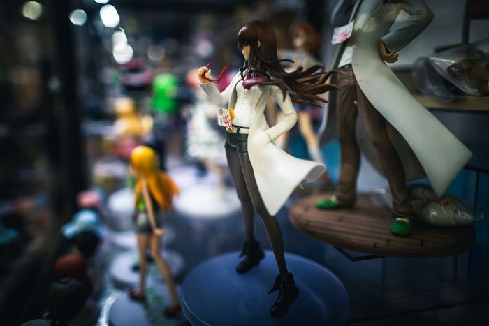 A plastic figure of a woman on a shelf with other toys