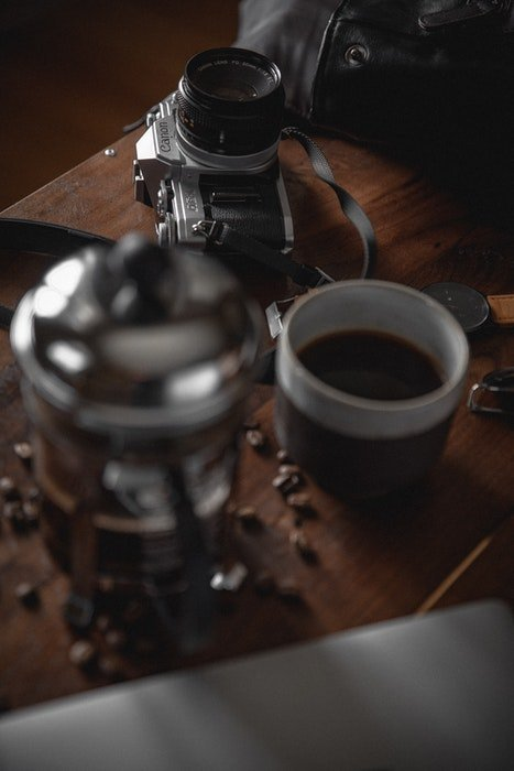 Photo of a camera and a mug of coffee on a wooden table