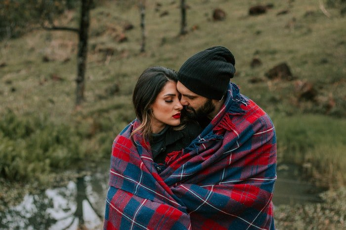 A couple embracing outdoors, a checked blanket around them