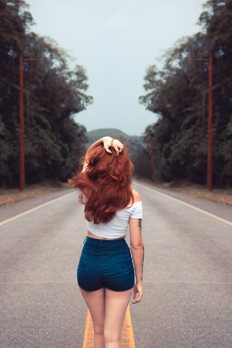 A girl facing away from the camera on a road