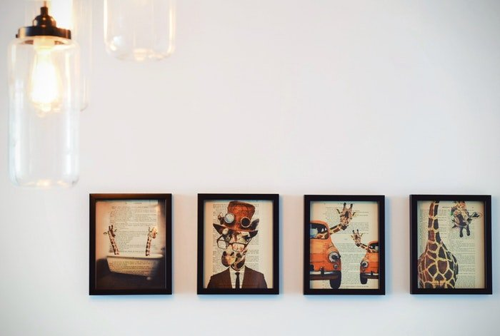 Four framed prints of quirky artwork on a wall