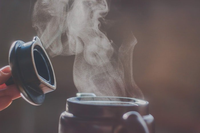 A close up of steam pouring out of a coffee pot