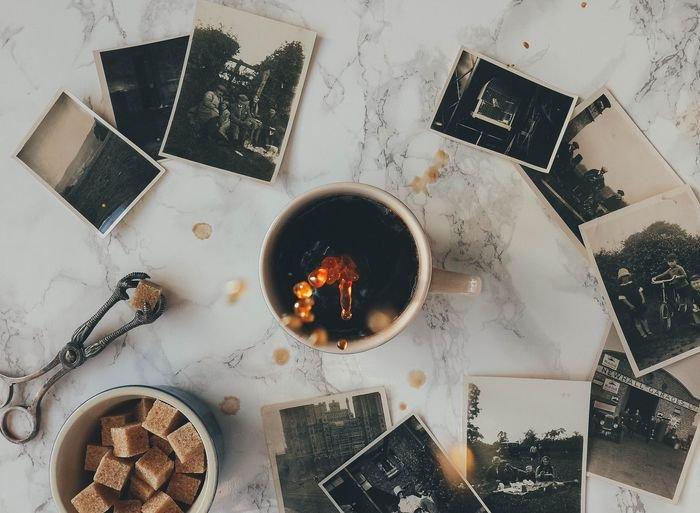 overhead photo of a coffee mug on a table with black and white polaroid photos