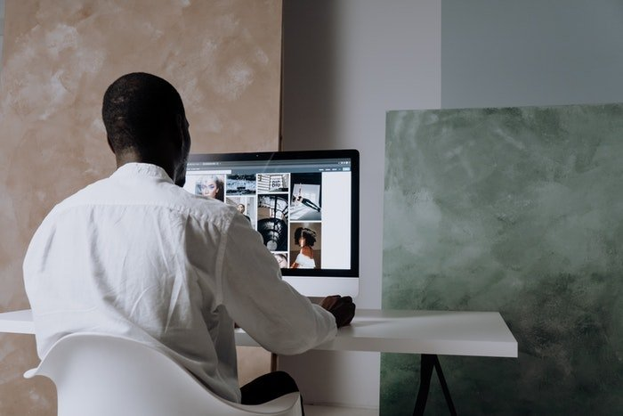 Man sitting by a computer with images on the screen