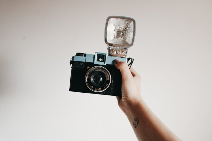A person holding a vintage camera with an external flash