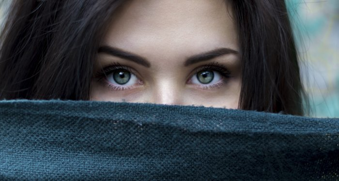 portrait photo of a girl with half of her face covered by a dark fabric
