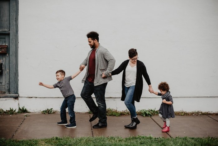 A couple with two young kids holding hands outdoors