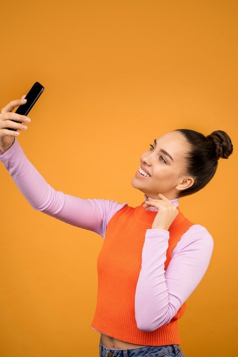 A young woman posing for a high angle selfie in front of an orange background