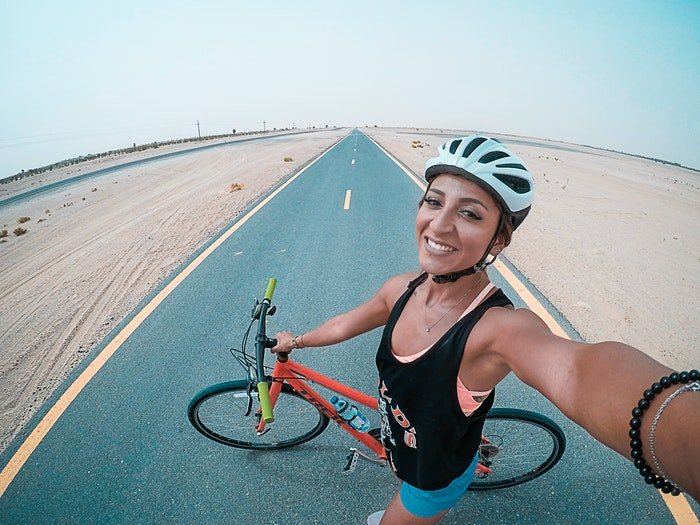 A girl taking a selfie while biking