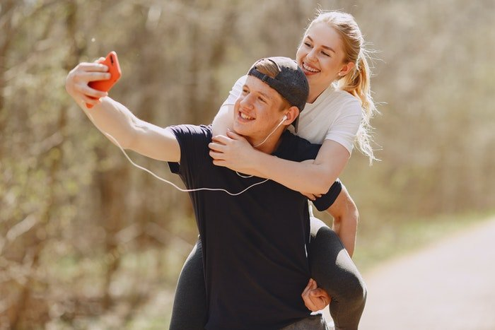 A young man takes a selfie with his girlfriend piggybacking his shoulders