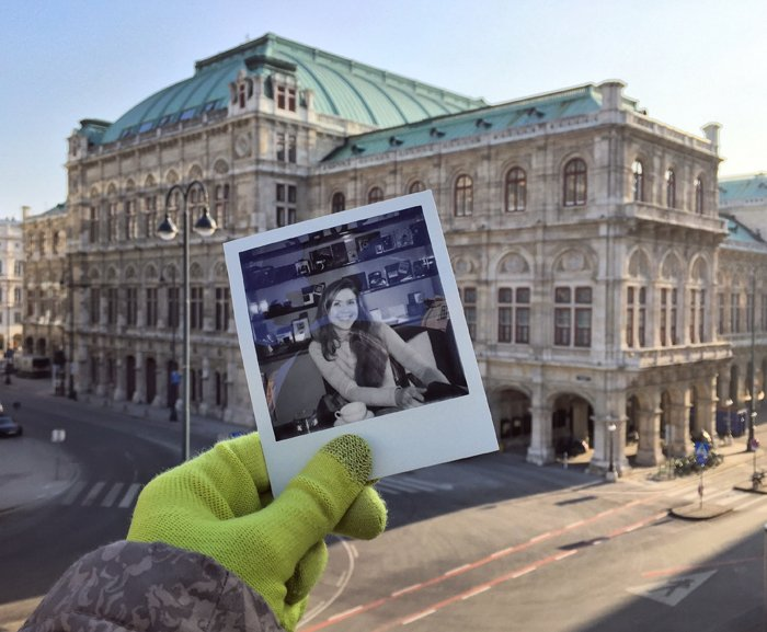 A Polaroid photograph of a smiling girl held in front of the Viennese Opera House in the background