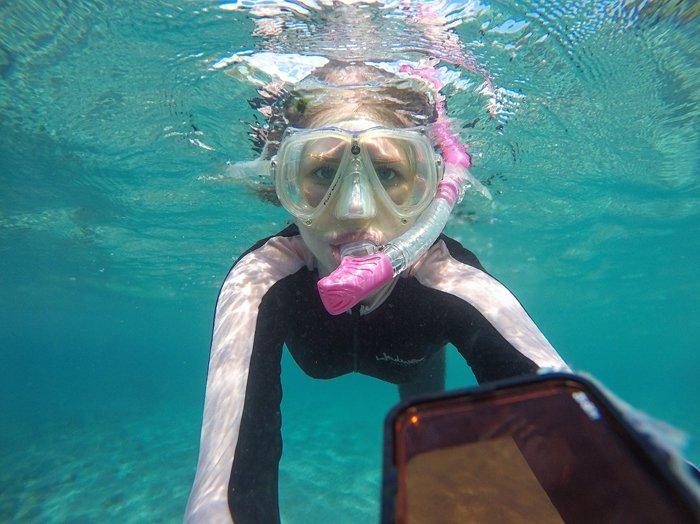 A snorkeling girl taking a selfie underwater