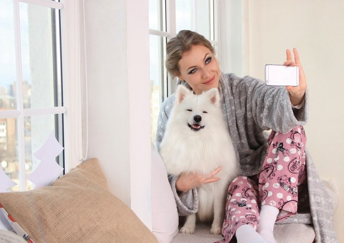 A pretty girl posing for a selfie with a cute fluffy dog