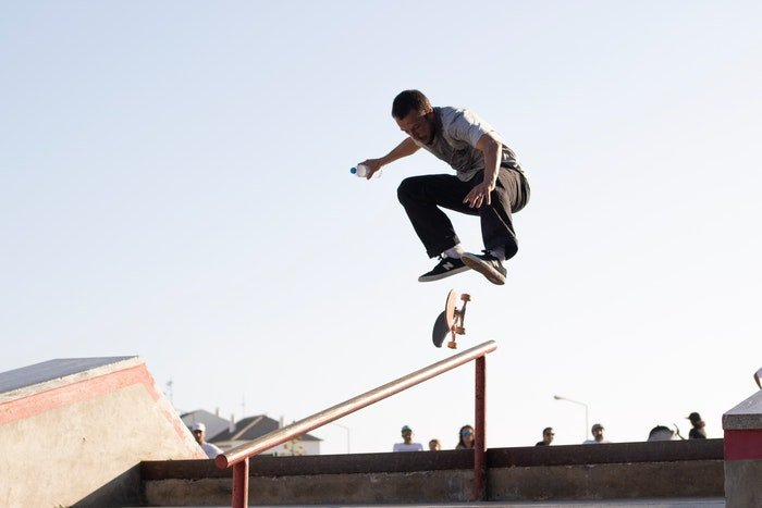 photo of a skateboarder in a park doing a jump trick