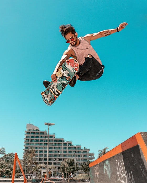 photo of a jumping skateboarder against the blue sky