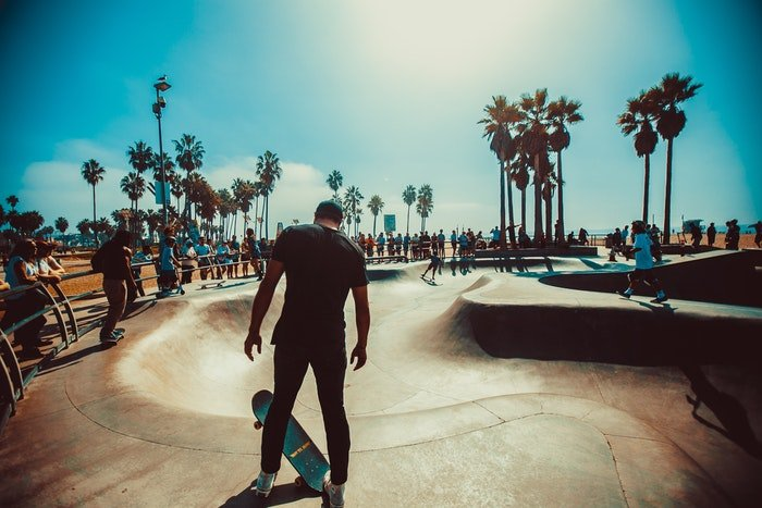 photo of a skateboarder standing on the edge of the ramp