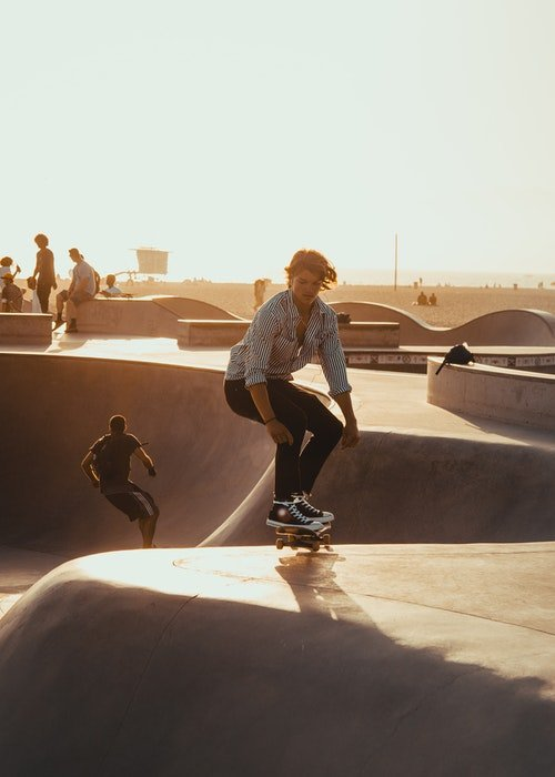 photo of a skateboarder in a park at sunset