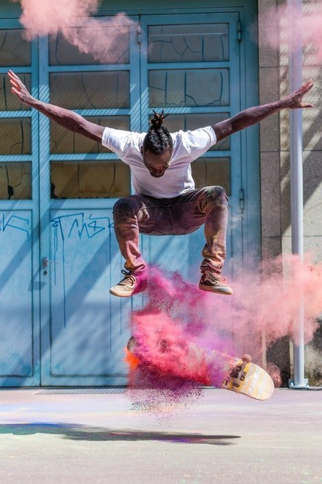 photo of a skateboarding doing a trick with color powder