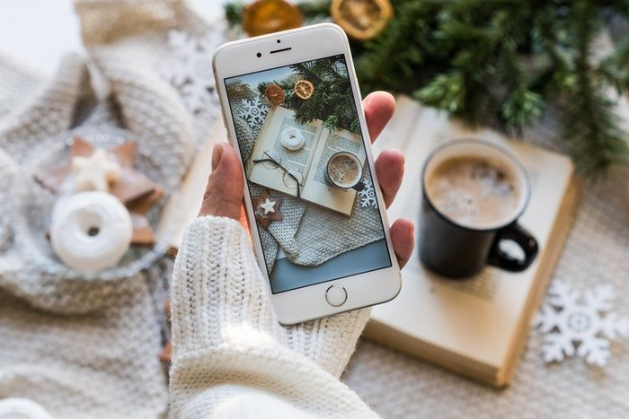 A person taking a still life photo on a smartphone