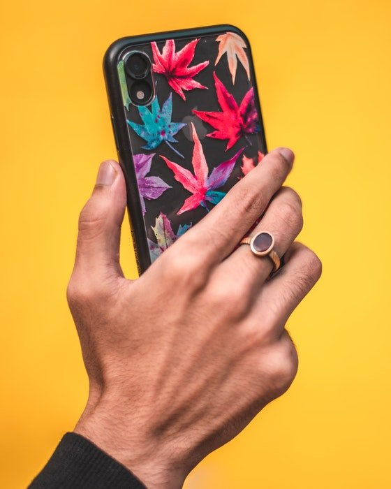A person holding a smartphone with a brightly colored case