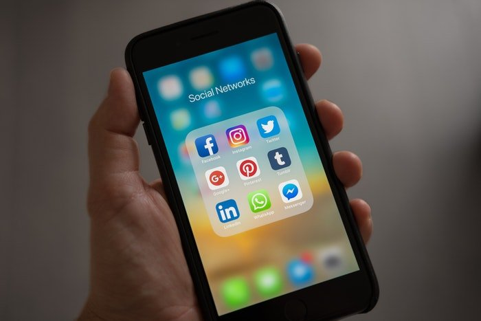 A person holding there smartphone opened on social media apps folder