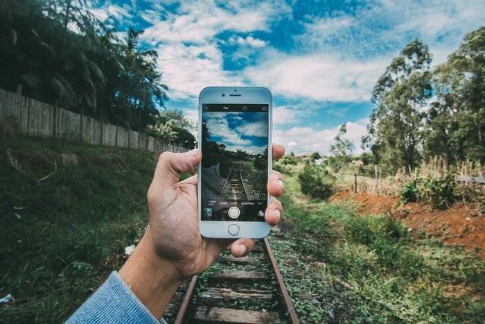A person taking a smartphone photo of train tracks
