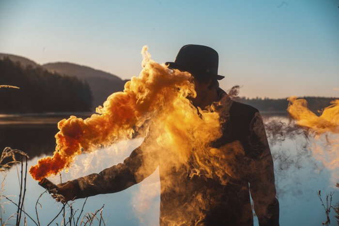A man holding a smoke grenade emitting bright yellow smoke in front of a landscape