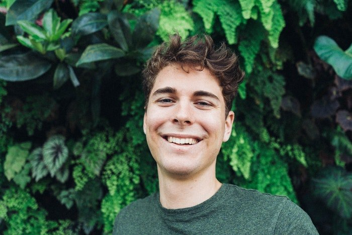 A young man infront of a green background