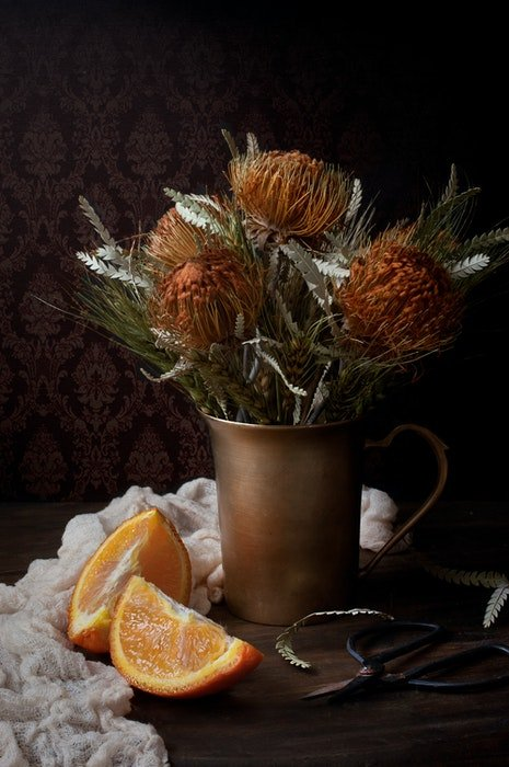 A cool still life composition of a bouquet of flowers in a copper vase