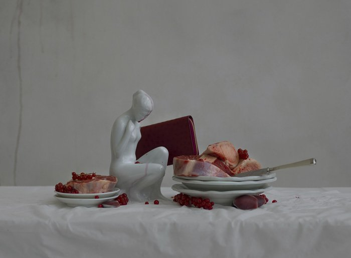 abstract still life photo with a small sculpture and two plates of food