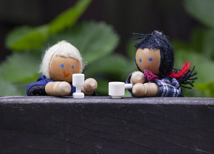 Cute toy photography of two wooden dolls dressed as old women drinking tea
