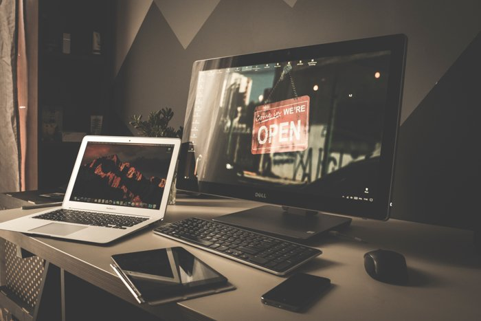 A picture of a desk with devices like a laptop and monitor