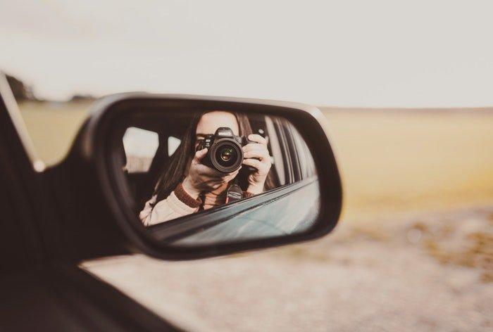 A girl taking a self portrait in a car side mirror