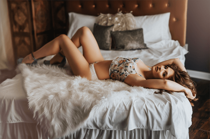 Boudoir portrait of a blonde woman in lingerie lying back on a bed