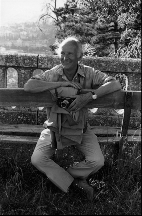 a black and white image of henri cartier-bresson sitting on a bench in forcalquier france in 1972